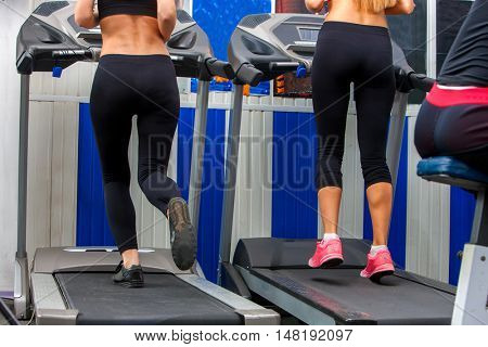 Middle section of running woman on treadmil at gym. Cardio workout of group girls.