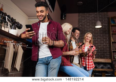 People Friends Using Cell Smart Phone, Drinking Orange Juice Talking Laughing Sitting At Bar Counter, Mix Race Man And Woman Happy Smile Network Communication