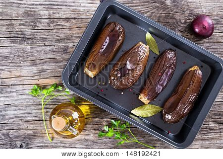 oven baked eggplants in baking dish with bay leaves and spices on woden boards view from above