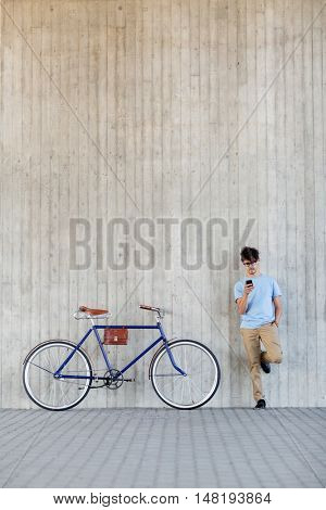 people, communication, technology, leisure and lifestyle - hipster man with smartphone and fixed gear bike on city street