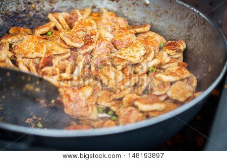 cooking, asian kitchen, sale and food concept - close up of meat frying in wok pan at street market