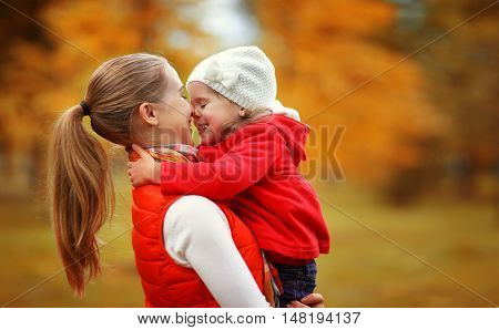 happy family. mother and child little daughter play kissing on autumn walk in nature outdoors