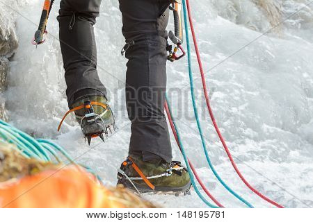 Close up of Ice climbing mountaineer legs with professional sport boots ropes and equipment
