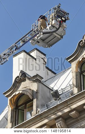 Firemen on a crane fixing a structural building fissure. Working people