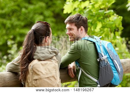 travel, hiking, backpacking, tourism and people concept - smiling couple with backpacks in nature looking and talking to each other