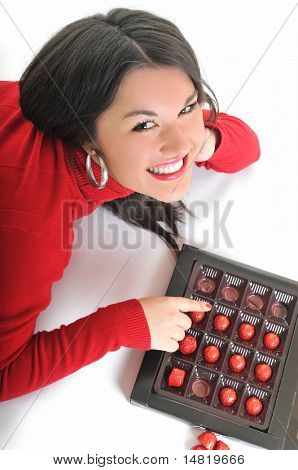 young beautiful brunette woman in red isolated on white eat chocolate food