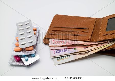 Money in brown wallet with blisters of pills. High cost of healthcare and medication concept.