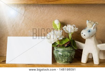 White card on wooden shelf with jasmin flower and pegasus.
