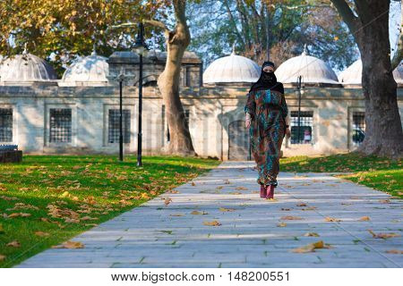 An attractive Young woman wearing a colorful head covering and Muslim Dress Walking on Alley in Autumnal Yard of Mosque