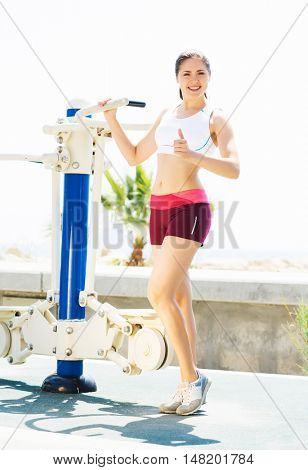 Fit and sporty woman training outside. Girl exercising on a sport machine in outdoor gym.