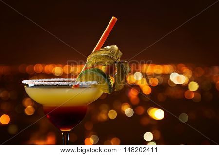 Cocktail with physalis and lime on a background of hight city