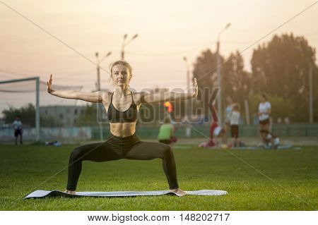 Young attractive woman exercising yoga outdoors. Goddess Pose.