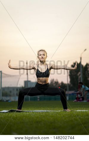 Young attractive blonde woman doing yoga exercises outdoors.Goddess Pose.