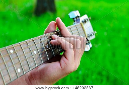 Man plays chords. Men's fingers and guitar strings