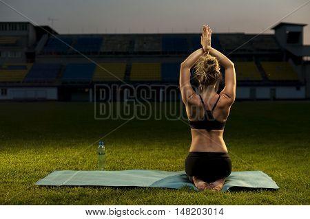 Slim blonde woman in black sportswear doing yoga outdoors. Thunderbolt Pose.