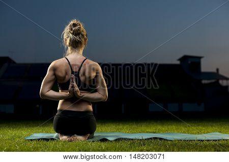 Flexible young woman doing yoga exercises on green grass. Thunderbolt Namaste Pose.