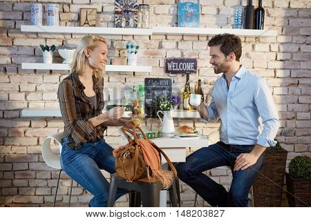 Young couple sitting in cafeteria, talking, drinking coffee.