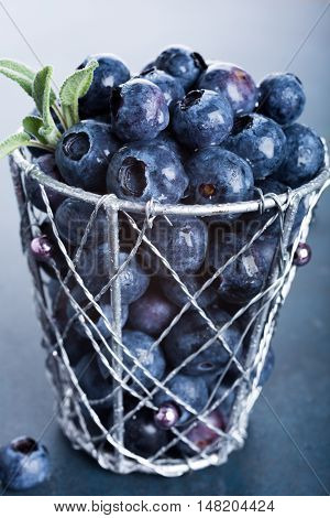 Freshly picked blueberries in metallic cup on blue background. Concept for healthy eating and nutrition