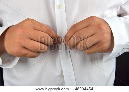 Young Man Buttoning His White Shirt On A Dark Background. He Is Dressing In The Morning. Clothes Det