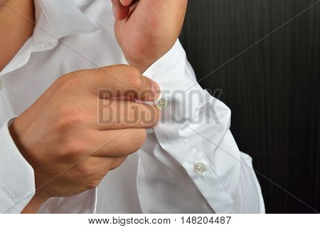 Close Up Of Hands Man How Closes Buttons On His White Sleeve Shirt At Home. Clothes Detail. Lights A