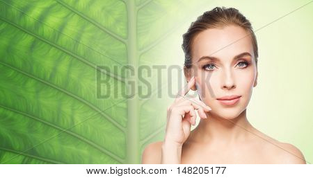 beauty, people and skin care concept - beautiful young woman showing her cheekbone over natural green leaf background
