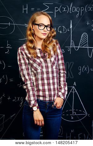 Portrait of a pretty student girl in spectacles standing by a school blackboard. Education, high school, college.