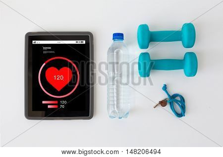 sport, healthy lifestyle, fitness and technology concept - tablet pc computer with heart rate on screen, dumbbells with whistle and water bottle over white background