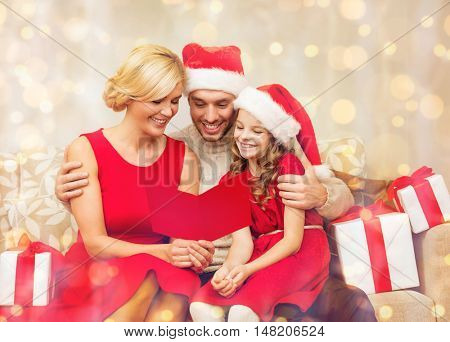 family, christmas, x-mas, winter, happiness and people concept - smiling family in santa helper hats with many gift boxes reading postcard