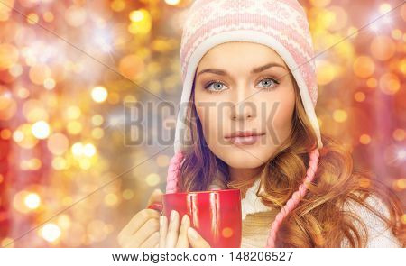 holidays, christmas, drinks and people concept - close up of young woman in winter clothes with red tea cup over lights background