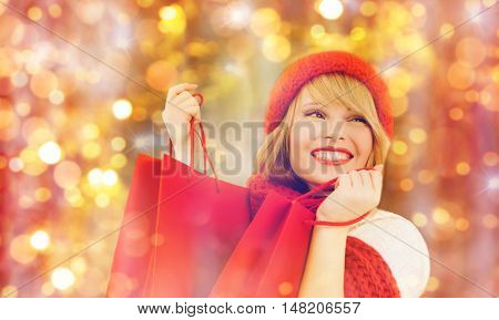 holidays, christmas, sale and people concept - happy smiling young woman in winter clothes with shopping bags over lights background