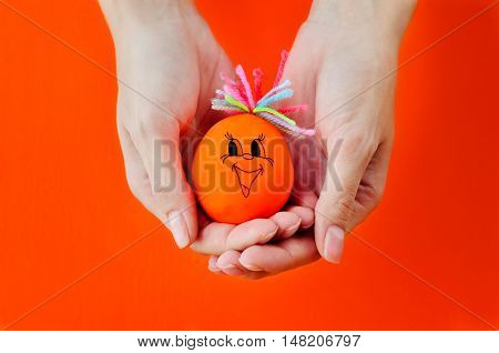 Bright toy with a smile in female hands on a bright orange background. Toy for the babie's development