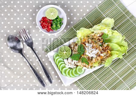 Fried rice with crab topped streamed crab,halve green lemon,sliced cucumber,lettuce and coriander  served  spicy  sour filling side dish.  Top view