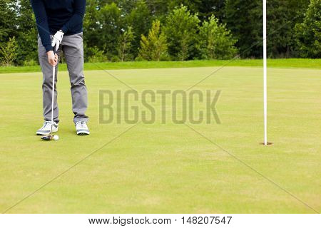 Male golf player drivers the ball into the hole