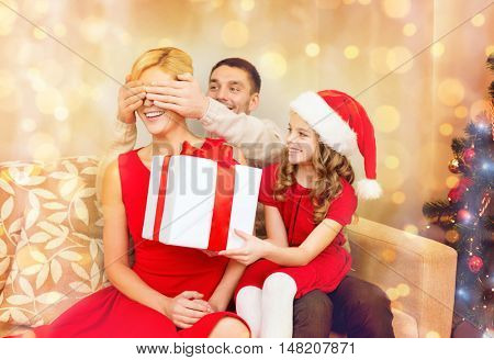 family, christmas, x-mas, winter, happiness and people concept - smiling father and daughter surprise mother with big gift box