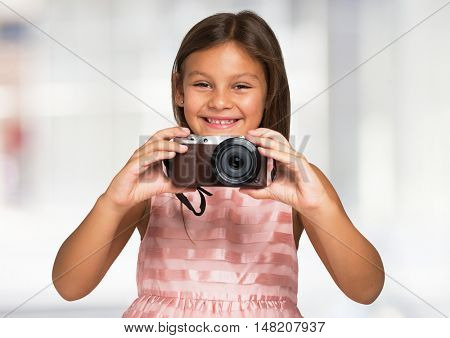 Smiling child holding a compact camera. Bright blurred background