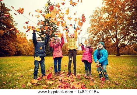childhood, leisure, friendship and people concept - group of happy kids playing with autumn maple leaves and having fun in park