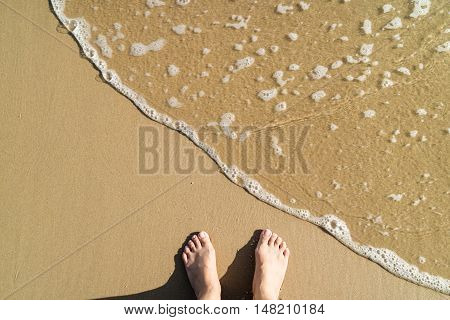 Woman Feet Standing On The Beach With Waving Sea