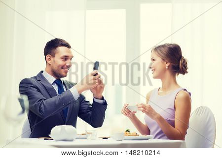 restaurant, couple, technology and holiday concept - smiling man taking picture of wife or girlfriend while picturing sushi with smartphone