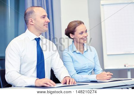 business, people and teamwork concept - smiling businesspeople meeting on presentation in office