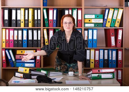 Cute Business Woman staying at Office Desk pointing Hand on large Stack of Paperwork in Folders Binders Smart Casual Clothing black shirt