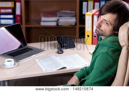 Young bearded Business Person in Casual Clothing sitting at Chair in Office at working desk with Laptop Papers Telephone Coffee Mug Binders and Folders