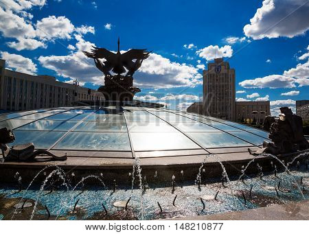 Minsk Belarus: August 25 2016: Three storks sculpture in the fountain in Independence Square backlighting