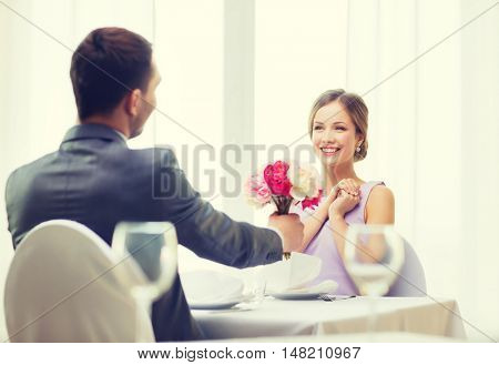 restaurant, couple and holiday concept - smiling woman recieving bouquet of flowers from husband or boyfriend at restaurant
