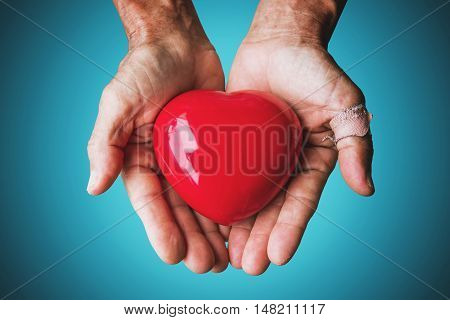 Elderly hand with wound carrying red heart