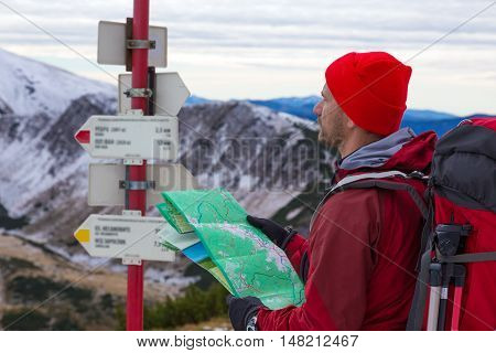 Hiker with Backpack and other Gear staying on Trail at Road Sign holding Paper Map and trying to orientate and find Direction