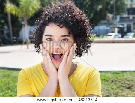 Surprised caucasian girl with curly black hair outdoor in the city in the summer