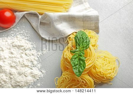 Dry pasta nests with basil on table