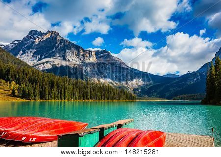 Shiny red kayaks are dried upside down. Emerald Lake in the Canadian Rockies. The concept of leisure and tourism