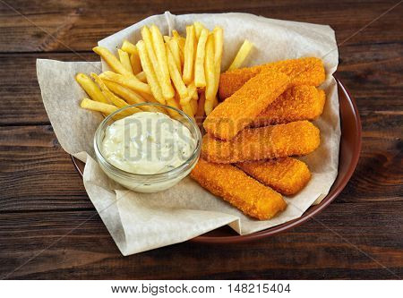 Plate with tasty fish nuggets, fries and sauce on wooden table
