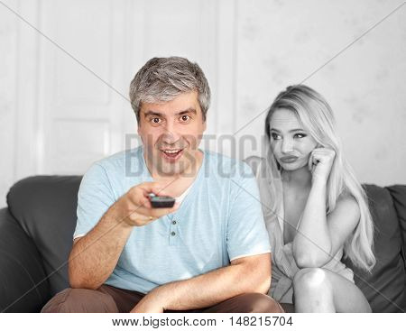 Man switching TV channel on remote control boring wife and marriage dependent selective coloring